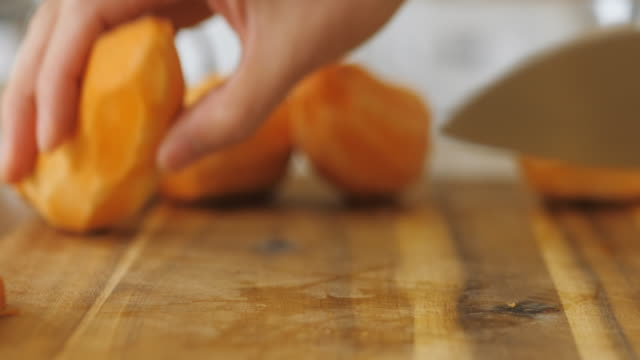 木製のまな板にサツマイモをくさびに手で切る - サツマイモ点の映像素材/bロール