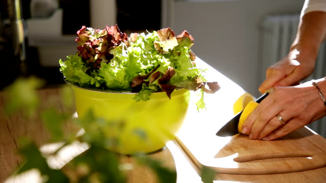 hand cutting lemon in half to season salad, slow motion - salad bowl stock videos & royalty-free footage