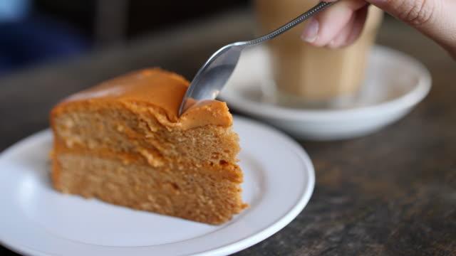 vídeos y material grabado en eventos de stock de mano cortando el pastel de naranja a café café, cámara lenta - pastel dulce