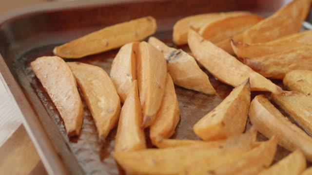 hand cutting sweet potato wedge on wooden board - sweet potato stock videos & royalty-free footage