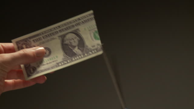 CU Hand cutting up U.S. one dollar bill with scissors