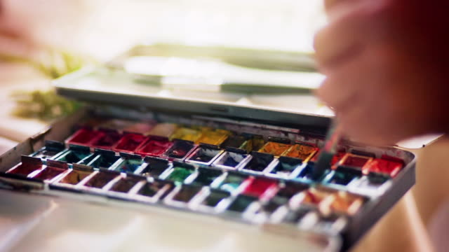 hand dipping paintbrushes into a watercolor paint box. - group of objects stock videos and b-roll footage