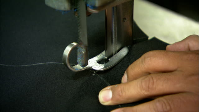 a hand directs an electric cutting tool and follows a pattern around a thick piece of fabric. - textile stock videos & royalty-free footage