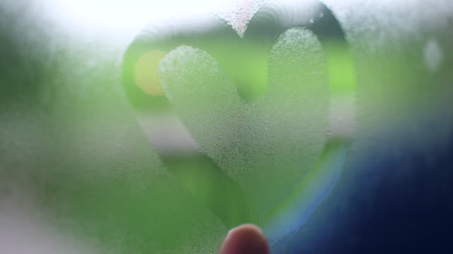 hand drawing heart with fingers on steamed window with green rice paddy on background - condensation stock videos & royalty-free footage