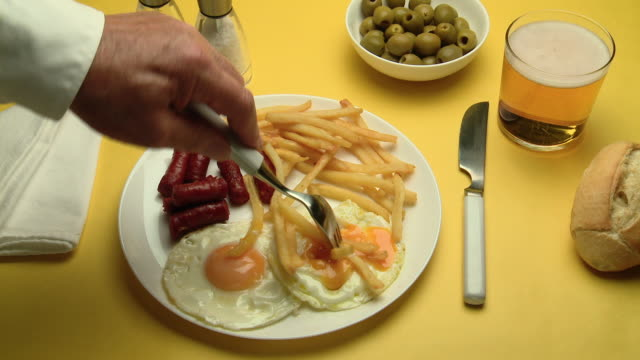 CU Hand eating Chorizo, eggs & chips with drink