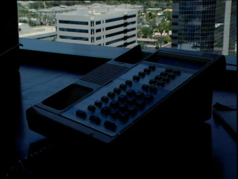 vídeos de stock, filmes e b-roll de hand emphatically puts handset back on telephone in shadowy office with office buildings in background california - estilo dos anos 2000