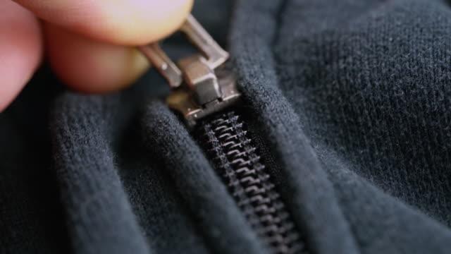 手はグレーブルーのスポーツジャケットに黒いプラスチックのジッパーロックを締め付け - 生地サンプル点の映像素材/bロール