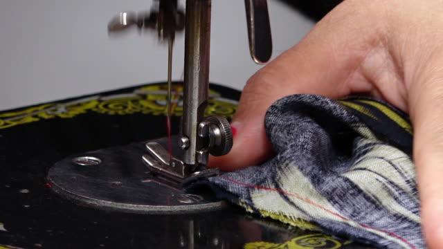 vídeos de stock, filmes e b-roll de hand feeding cloth through sewing machine - ponto de costura