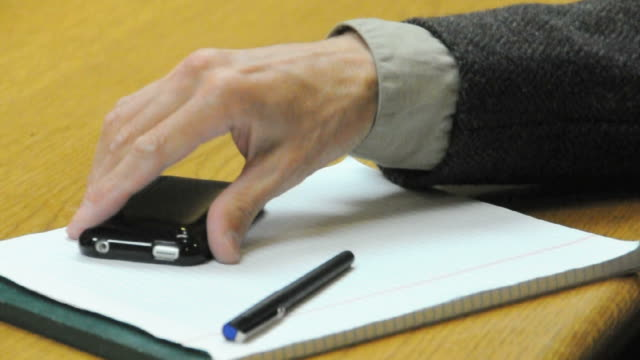 CU Hand fidgeting with pen and cell phone, Los Angeles, California, USA