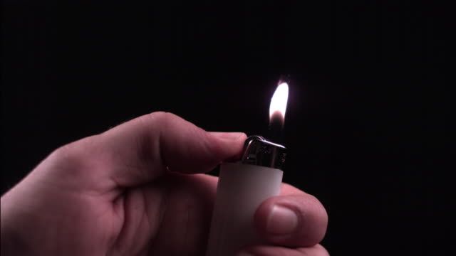 SM CU Hand flicking disposable lighter to cause flame against black background/ Auckland, New Zealand