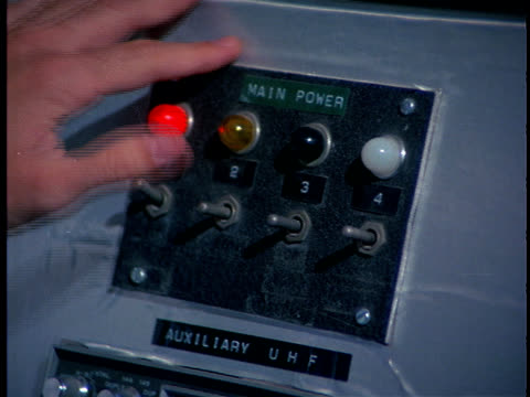 A hand flips four switches on a control  panel.