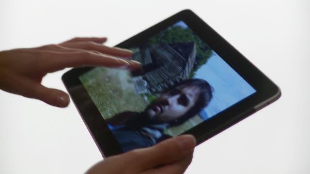 CU Hand flips through photos on tablet computer / Brooklyn, New York, USA