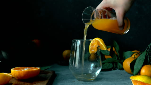 vídeos de stock e filmes b-roll de hand gently pour tangerine / orange juice from vintage bottle into a glass - fatia
