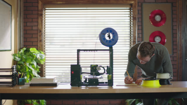 hand gestures at digital model on computer screen as camera pans to 3d printer manufacturing object and young engineer taking notes in modern office. - 3d printing stock videos & royalty-free footage