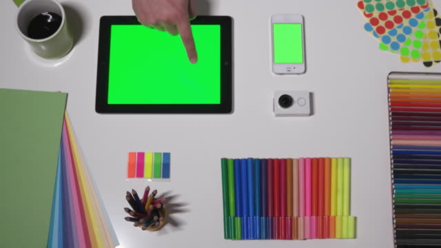 Hand gestures of a man on a green-screen touchscreen tablet with a colourful table