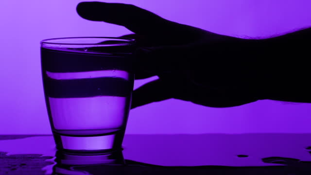 hand grab glass full of water and spill some of the water - purple background - overflowing stock videos & royalty-free footage