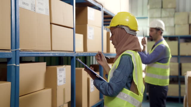 4k uhd hand held : asian islam muslim female warehouse worker checking inventory and shipping route with clipboard for warehouse goods logistic concept - oregon coast stock videos & royalty-free footage