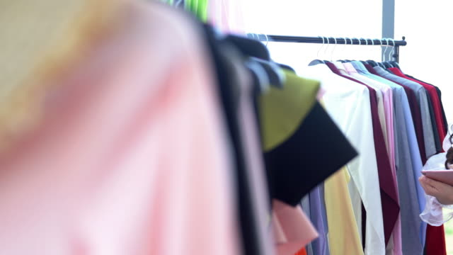 hand held dolly shot: tailor fashion designer working at home with technology digital tablet - atelier fashion stock videos & royalty-free footage