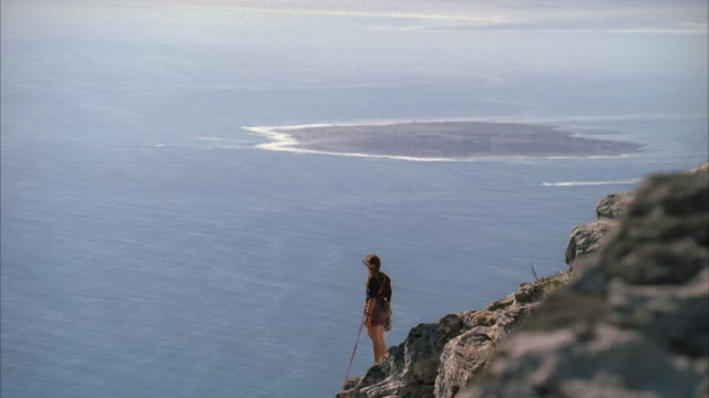 Hand held shot of a woman standing on the edge of a cliff looking out towards the sea and Robben Island