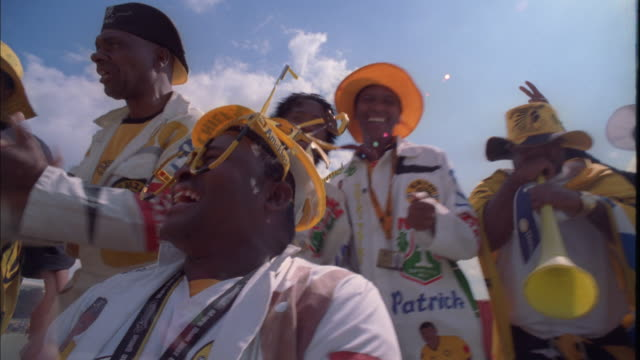 hand held shot of kaizer chiefs fans in colourful outfits clapping and singing, johannesburg available in hd. - cantare video stock e b–roll