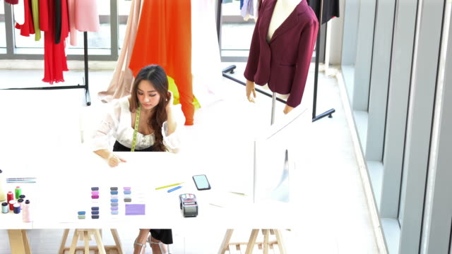 hand held top view: tailor fashion designer working at home with technology digital tablet - atelier fashion stock videos & royalty-free footage
