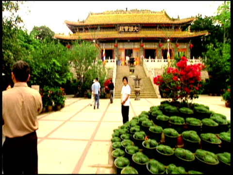 stockvideo's en b-roll-footage met hand held track forward across courtyard up steps and into temple to shrine surrounded by flowers lantau island - gelovige