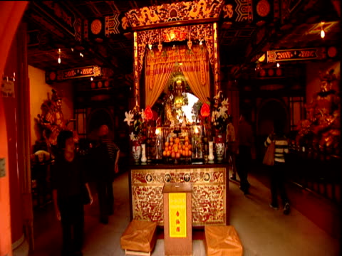 hand held track forward into temple around shrine with statues fruit and flowers lantau island - lantau stock videos and b-roll footage