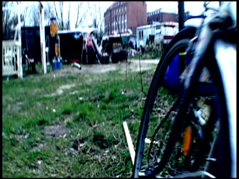 hand held track forward through travellers camp where berlin wall once stood past bikes portaloos and abstract wooden sculpture - new age stock videos & royalty-free footage