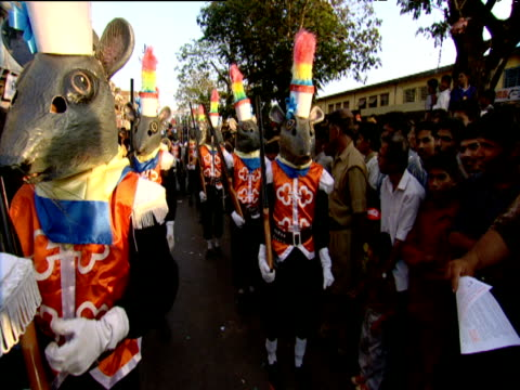 Hand held track through line of people in mouse costumes during carnival Goa