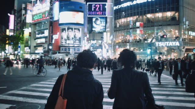 MS, Hand held travelling shot of the Shibuya crossing at night