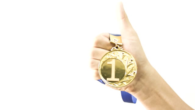 Hand hold gold medal.