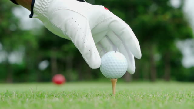 hand hold golf ball with tee on golf course - drive ball sports stock videos & royalty-free footage