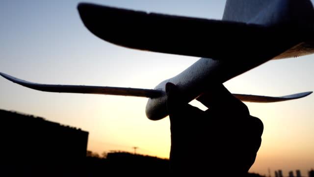 vídeos y material grabado en eventos de stock de mano mantenga el avión de papel al atardecer - avión de papel