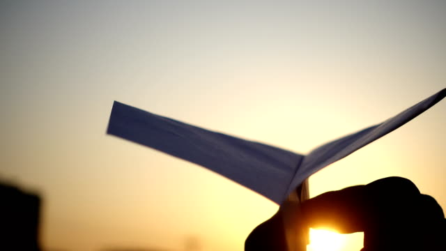 vídeos de stock e filmes b-roll de hand hold paper airplane at sunset - arremessar