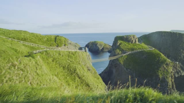 hand hold shoot view of  carrick-a-rede rope bridge  in northern ireland - northern ireland stock videos & royalty-free footage