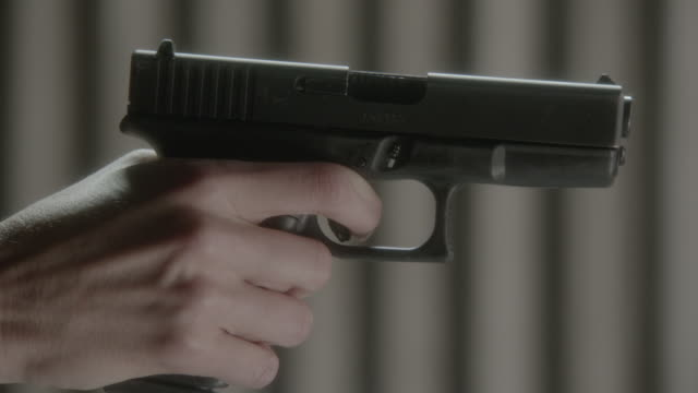 cu hand holding 9mm handgun drops from and rises into frame - aiming stock videos and b-roll footage
