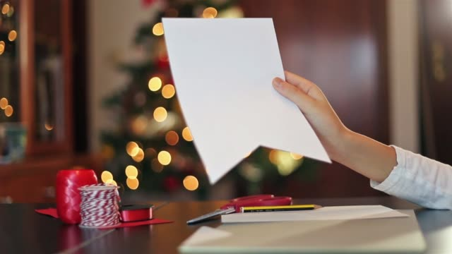hand holding a greeting card in process in front of the christmas tree. - parte de una serie video stock e b–roll