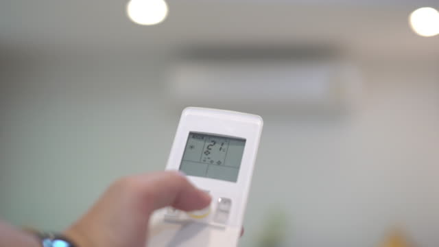 tenere a mano un telecomando e regolare la temperatura del condizionatore d'aria. - remote control video stock e b–roll