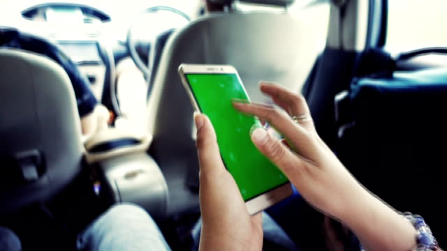 a hand holding a smartphone with green blank screen in the car. - blank screen stock videos & royalty-free footage