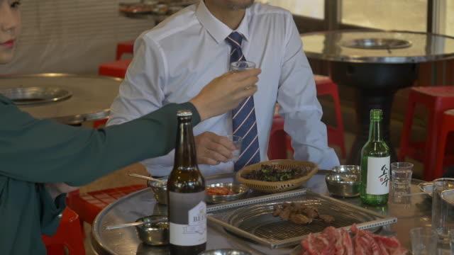hand holding a soju (korean alcohol) glass - skjorta och slips bildbanksvideor och videomaterial från bakom kulisserna
