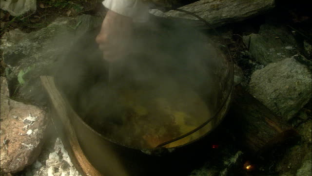 a hand holding a spoon stirs steaming liquid in an old-fashioned pot. - stirring stock videos & royalty-free footage