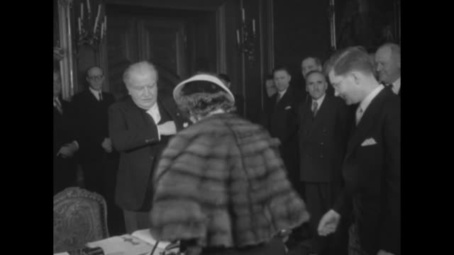 cu hand holding agreement in which luxembourg gives cemetery to us / shot of chandelier in room where ceremony is held tilt down to perle mesta us... - 1951 stock-videos und b-roll-filmmaterial