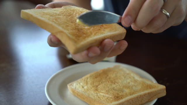 hand holding bread and butter making for breakfast - butter stock videos and b-roll footage