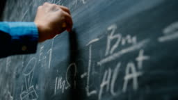 Hand Holding Chalk and Writing Complex and Sophisticated Mathematical Formula/ Equation on the Blackboard.