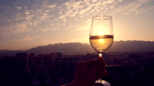 Hand holding champagne at sunset