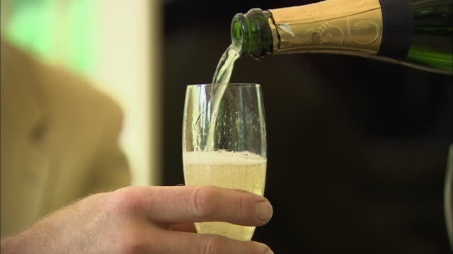 CU Hand holding champagne glass while champagne being poured into glass / Paris, Ile-de-France, France