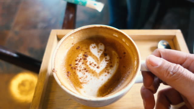 pov of hand holding coffee cup and pick up to drink an paste back on table in coffee shop - point of view video stock e b–roll