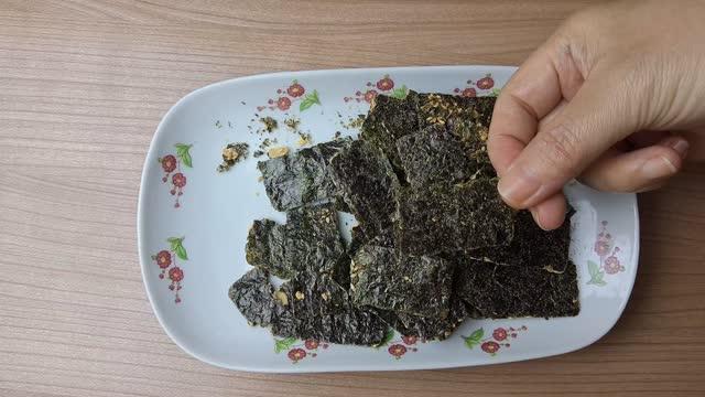 hand holding getrocknetlaminaria algen snack - kelp stock-videos und b-roll-filmmaterial