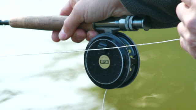 cu hand holding fly fishing reel / devon, england, united kingdom - wiese stock videos & royalty-free footage