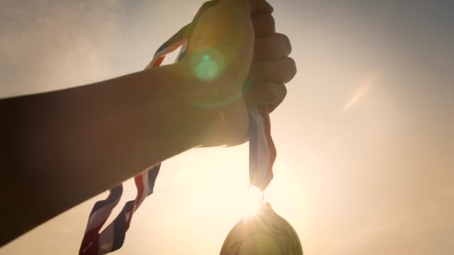 hand holding gold medal up - award stock videos & royalty-free footage